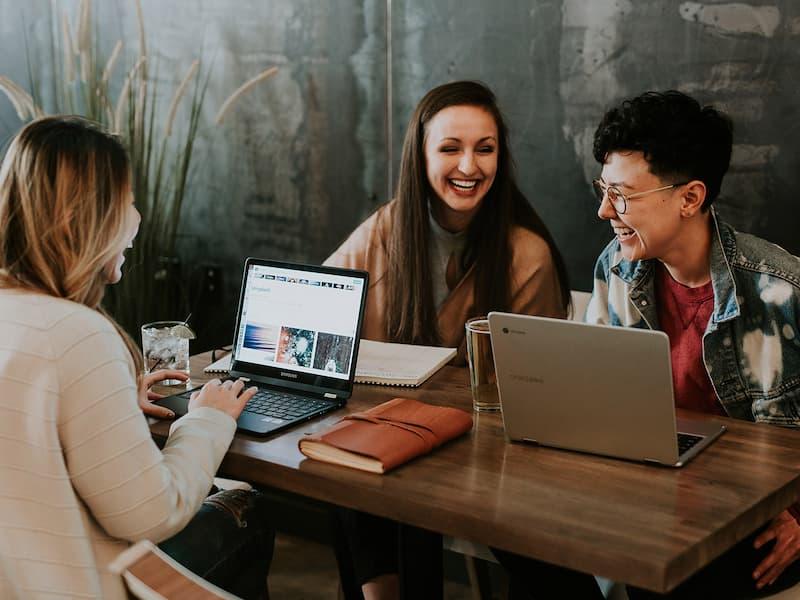 Drei junge Leute vor aufgeklappten Laptops in einem Café in Schweinfurt
