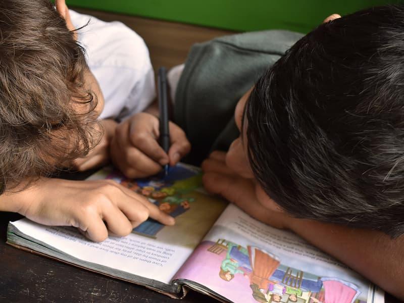 Zwei Kinder malen in ein Schulbuch